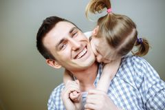 Dad and his daughter child girl are playing, smiling and hugging. Family holiday and togetherness. Shallow depth of field. Dad and his daughter child girl are stock photography