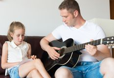 Dad and his daughter compose a song. Dad and his daughter compose a song on the guitar stock photos