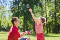 Dad and his daughter are making bubbles Stock Photos