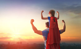Dad and his daughter playing outdoors. Happy loving family. Dad and his daughter playing outdoors. Daddy and child girl in an Superhero`s costumes. Concept of Stock Image