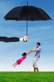 Dad and his daughter playing under umbrella at field. Image of young father playing on the meadow with his daughter under umbrella. Life and family insurance Stock Image