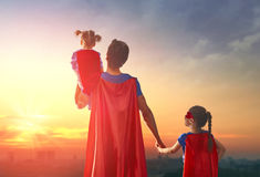 Dad and his daughters are playing. Happy loving family. Dad and his daughters are playing outdoors. Daddy and his children girls in an Superhero`s costumes royalty free stock photos