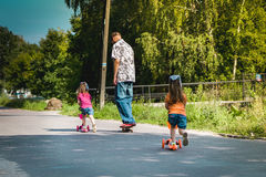 Dad with his daughters on a skateboard and scooter Royalty Free Stock Photo
