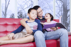 Dad and his kids reading book on sofa. Young asian father sitting on the sofa while reading a book with his children, shot with winter background on the window royalty free stock photography