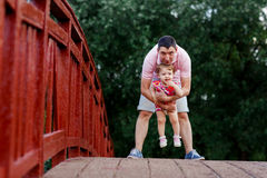 Dad with his little daughter standing on wooden bridge Royalty Free Stock Photography