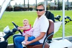 Dad and his little daughters driving golf cart Royalty Free Stock Photography
