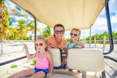 Dad and his little girls driving golf cart on Royalty Free Stock Images