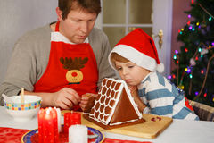 Dad and his little son decorating a gingerbread cookie house. At christmas time. With light Christmas tree on background royalty free stock photography