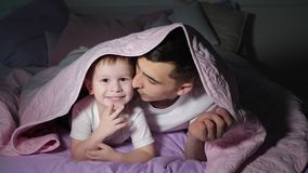 Dad and his little son is playing hiding under the blanket in dark. Dad and his little smiling son is playing hiding under the pink blanket in dark laying on stock images