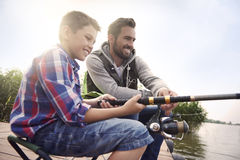 Dad with his son fishing together. Fishing by the lake is our common passion royalty free stock images