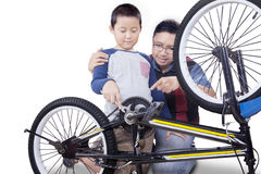 Dad and his son fixing a bicycle Royalty Free Stock Photos