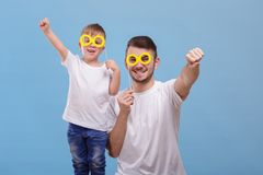 Dad and his son put their glasses on a stick on a blue background stock image