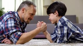 Dad and his son looking at each other and competing in force, playing game. Stock photo royalty free stock image