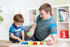Dad with his son play together. Dad with his son child play together at home stock photo
