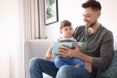 Dad and his son reading book on sofa. At home royalty free stock image