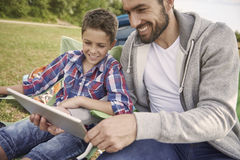 Dad with his son watching something on tablet Stock Photo