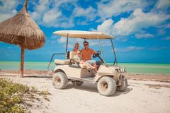 Dad and his two daughters driving golf cart on a Royalty Free Stock Image