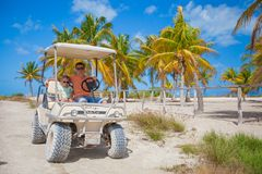Dad with his two daughters driving golf cart at Stock Image
