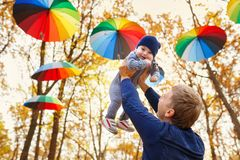 Dad holding baby girl in hands. Young father play with a little daughter in autumn park. Dad holding baby girl in hands stock images