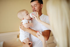 Dad holding a baby in her arms, mother feeds her baby son bottle. Parents feed a small child with a bottle holding it in their arms Stock Photography