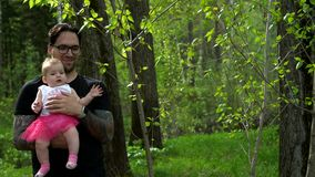Dad is holding a daughter in her arms. Dad and daughter are walking in the woods
