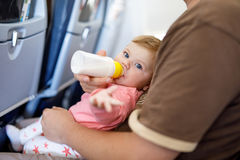 Dad holding his baby daughter during flight on airplane going on vacations Royalty Free Stock Photography
