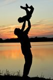 Dad holding son against the sunset Royalty Free Stock Images