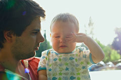 Dad is holding sweet crying baby boy. Back-lit with lens flare in the morning Royalty Free Stock Image