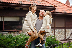 Dad is holding two charming sisters in the same curly beige knit royalty free stock photography