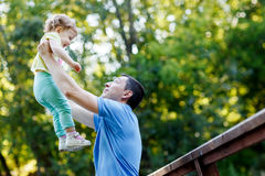 Dad holds baby daughter in his arms high in park. Dad holds baby daughter in his arms high in summer park Royalty Free Stock Photography