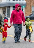 A dad holds the hands of two super heroes. October 27, 2018 Coloma MI USA; a dad holds the hands of two super heroes, as they walk down the street during a royalty free stock photo