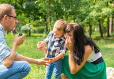 Dad holds his son`s hand and teaches him to blow soap bubbles. M Royalty Free Stock Image
