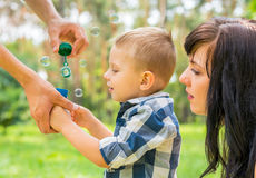 Dad holds his son`s hand and teaches him to blow soap bubbles. M Royalty Free Stock Images