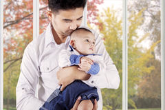 Dad holds and kiss his baby at home. Photo of a young asian father holding and kiss his little boy near the window at home Royalty Free Stock Photo