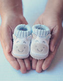 Dad holds shoes for newly born baby boy. Father holds in his palms knitted baby shoes for boy Stock Image