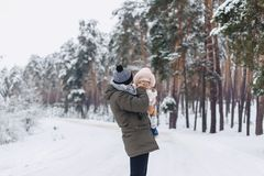 The dad holds a small daughter. On the snowy picturesque terrain in a pine forest on the highway Royalty Free Stock Photography