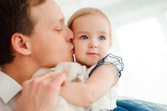 Dad hugging and kissing his little daughter. stock images