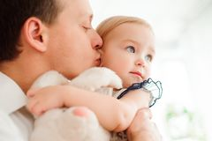 Dad hugging and kissing his little daughter. stock photo