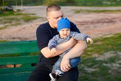 Dad hugs and kisses his displeased son on a bench in the park. Dad hugs and kisses his little displeased son son on a bench in the park stock images