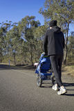 Dad jogging with baby stroller on a country road. Dad jogging or walking with baby stroller on a country road Royalty Free Stock Image