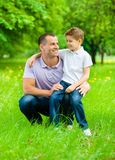 Dad keeps son on the knee. Father keeps son on the knee in the park. Concept of happy family relations and carefree leisure time Royalty Free Stock Photo