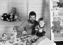 Dad and kid build of plastic blocks. Man with beard and boy play near toys and wooden wall on background. Father and son. With happy faces make house with stock photography