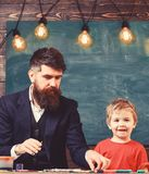 Dad and kid having fun at art class. Daddy and son painting together.  royalty free stock image
