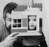 Dad and kid hide behind house made of colored blocks. Boy and bearded man play together. Family game and childhood. Dad and kid hide behind house made of colored stock photography