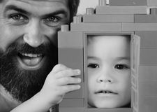 Dad and kid hide behind house made of plastic blocks. Boy and man play together, close up. Father and son. Dad and kid hide behind house made of plastic blocks stock photos