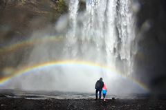 Dad and kid under the rainbow at the foot of Skogafoss heavy waterfall in Iceland royalty free stock photo