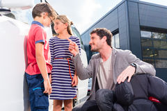 Dad with kids buying family car at dealer royalty free stock image