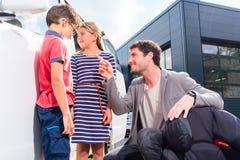 Dad with kids buying family car at dealer. At yard, a van Royalty Free Stock Image