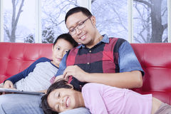Dad and kids enjoy leisure time on sofa. Young asian father enjoy leisure time with his children on sofa while using tablet, shot with winter background on the Stock Images