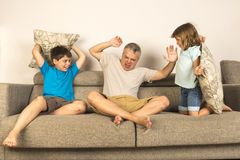 Dad and kids fighting together with pillows Royalty Free Stock Photo